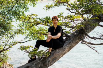 Emily Molnar sitting in a tree that extends over a river.