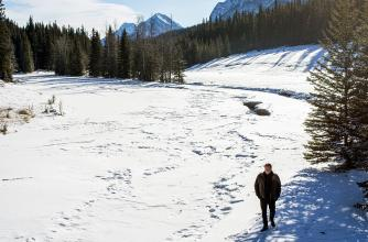 Jean Grand-Maître walks along a snow covered river.