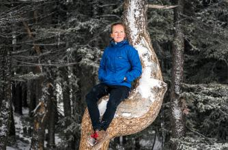 Kate Harris sits in a snow covered tree.