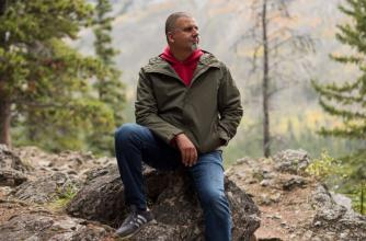 Marcus Youssef sitting on a rock in nature