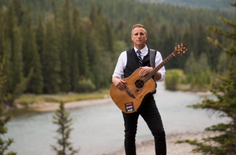 Sean McCann poses with guitar in front of a forest with a river.