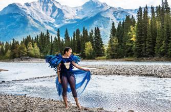 artist iskwē poses in front of a river forest landscape.