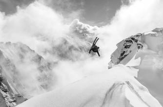 black and white photo of skier doing a back flip off a snowy ridge high up in the mountains