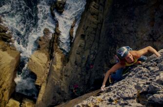 A female climber hanging over a cliff