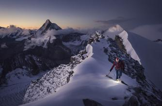 A mountaineer traversing across a snowy mountain ridge. Valentine Fabre, Dent Blanche, Switzerland. Photo by Ben Tibbetts
