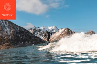 Surfer catches a wave with snow capped mountains in the background.
