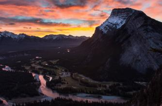 Sun rises behind Mt. Rundle as seen from Tunnel Mountain, the sky has fiery orange and bright pink clouds.