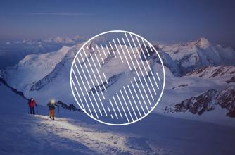 Two skiers with headlamps climbing along a mountain peak.