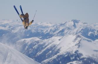 Skiier performs a backflip with a mountain range in the background.