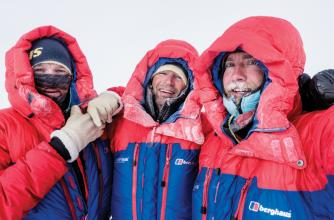 Three mountaineers grouped together in the cold.
