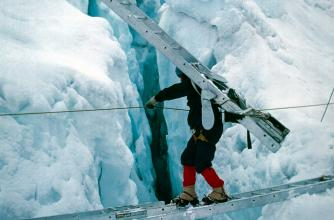 A lone mountaineer carries an aluminum ladder tied to his back while crossing an icy crevasse atop a second, aluminum ladder.  He holds a stable rope line strung across the break to keep from falling, as his unsure footing is worsened by his crampons.