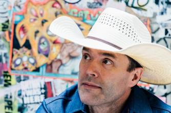 Corb lund wearing a formal denim shirt and white Stetson hat sits in front of a heavily stickered wall.