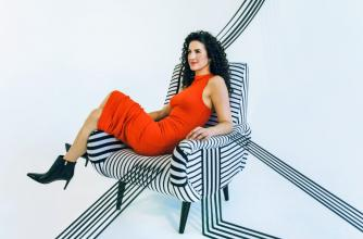 Canadian singer Laila Biali sits in a chair that appears to be an art installation with its stripes flowing off of it.