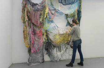An artist manipulates multi-coloured fabric draped from a wall.