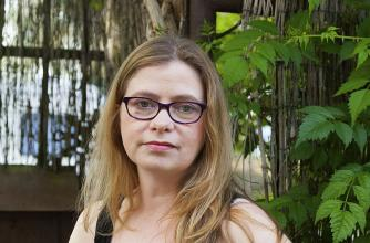 Author Arabella Campbell stands in front of outdoor greenery wearing a black tank top.