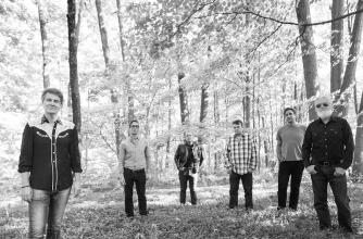 The six members of Blue Rodeo stand in the grass beneath a maple forest.