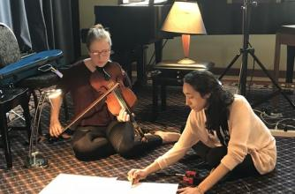 Two participants are seated on the floor. One annotates music while the other looks on holding a violin at the ready.