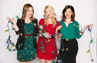 The three Ennis sisters wear read a green and are tangled up in Christmas lights.