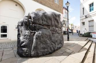 A semi-natural looking stone sits in the centre of a public square.