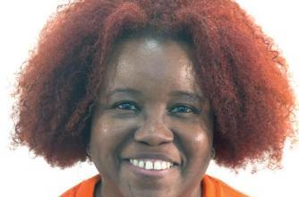 "Fatimah Tuggar Looks straight forward wearing an orange shirt that reads ""Art Papers"""