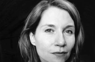 Author Jennifer Haig wears a plaid shirt in a headhsot.