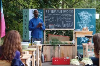 A man stands at the front of an informal outdoor classroom lecturing on Unkraut