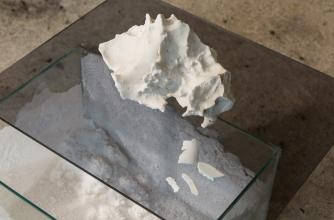 A many edged white stone sits atop a 3D glass rectangle with white sand inside the rectangle.