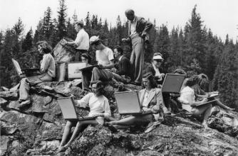 Black and white 1947 photo depicts instructor H.G. Glyde standing on a rock outcrop surrounded by art students who are facing outward and sketching.
