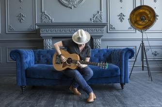 Irish sits on a blue felt couch wearing a broad rimmed hat playing her guitar.