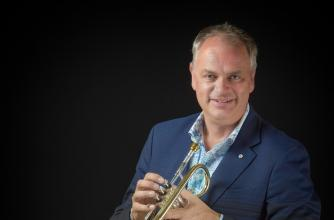 Jens Lindemann holds a trumpet wearing a suit jacket and jeans.