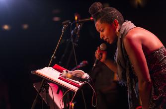A woman sings into a microphone on an informal stage.