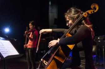 A young lady plays a cello in the foreground as another plays violin in the background, both are on stage performing.