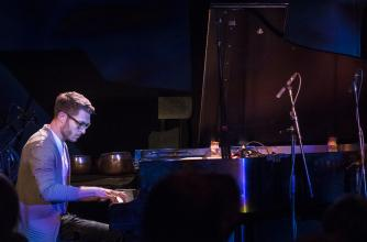 Young man plays a piano on an informal stage.