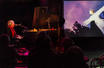 A woman plays a piano on stage with a projection video playing in the background.