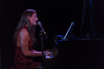 A woman wearing a red dress is seated playing the piano and singing into a microphone in an intimate setting.