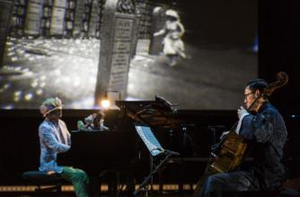 Two musicians are seated in front of a projected image wearing eclectic clothing, one plays the piano and the other a cello.