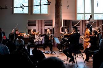 Eight participants play various quartet instruments before a crowd.