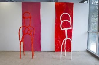 A Visual + Digital Art studio at Banff Centre, Banff National Park, Alberta. Two narrow abstract sculptures, one red and one white stand in front of a rough red a white background wall.