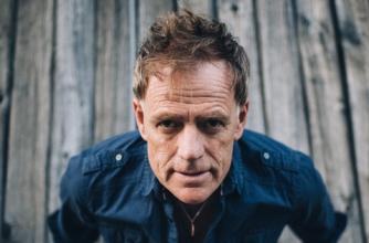 Martyn Joseph sits flat on a deck with his bands behind him propping himself up and looking at the camera.