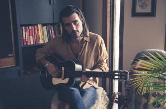 Reuben Bullock of Reuben and the Dark holds a guitar in a casual living room.