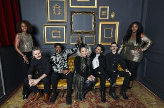 Samantha Martin and six members of Delta Sugar stand beside or sit on a gold velvet couch.
