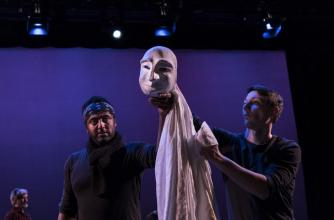 Two puppeteers in black hold up a white mask and costume.