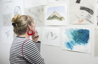 A woman views community art posted to a white wall.