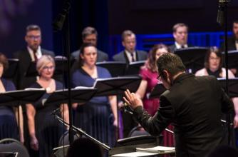 A choral conductor leads a choir in a formal setting.