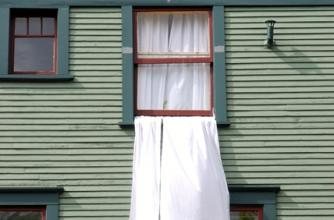 A long white curtain drapes out of half sliding window closed down over it, it is catching the wind.