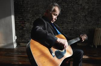 John Prine sits playing an acoustic guitar in an informal space.
