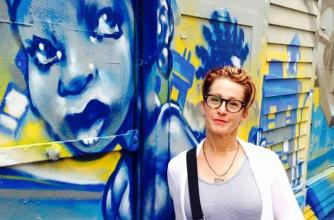 Author Lee Kvern stands in front of a graffiti wall.