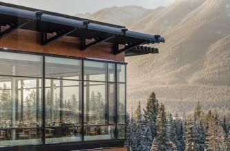 The floor to ceiling windows offer breathtaking views of the mountains.