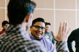 Photo shows Students in Introduction Negotiation Skills Training Course, one student stands to left with back to camera and right hand up and open as an another student looks forward to high five.
