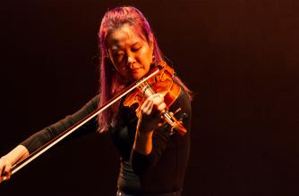 Female Violinist performing on a dark stage.